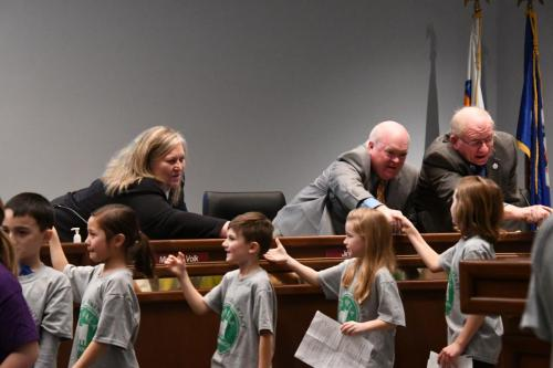 Lakeville School Board Members shake hands with students who sang at the meeting.
