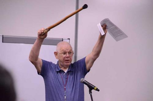 Man raising cane at education forum.
